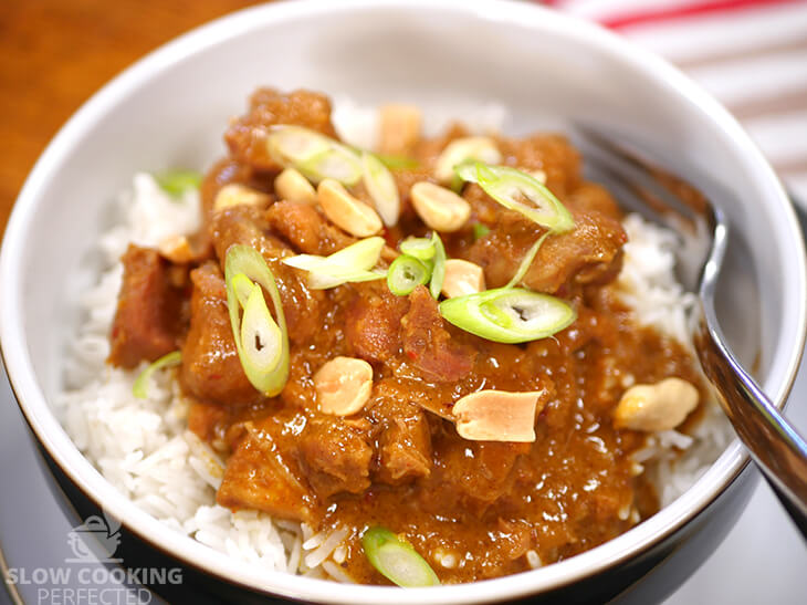 Slow-cooked Thai peanut chicken curry with rice and scallions